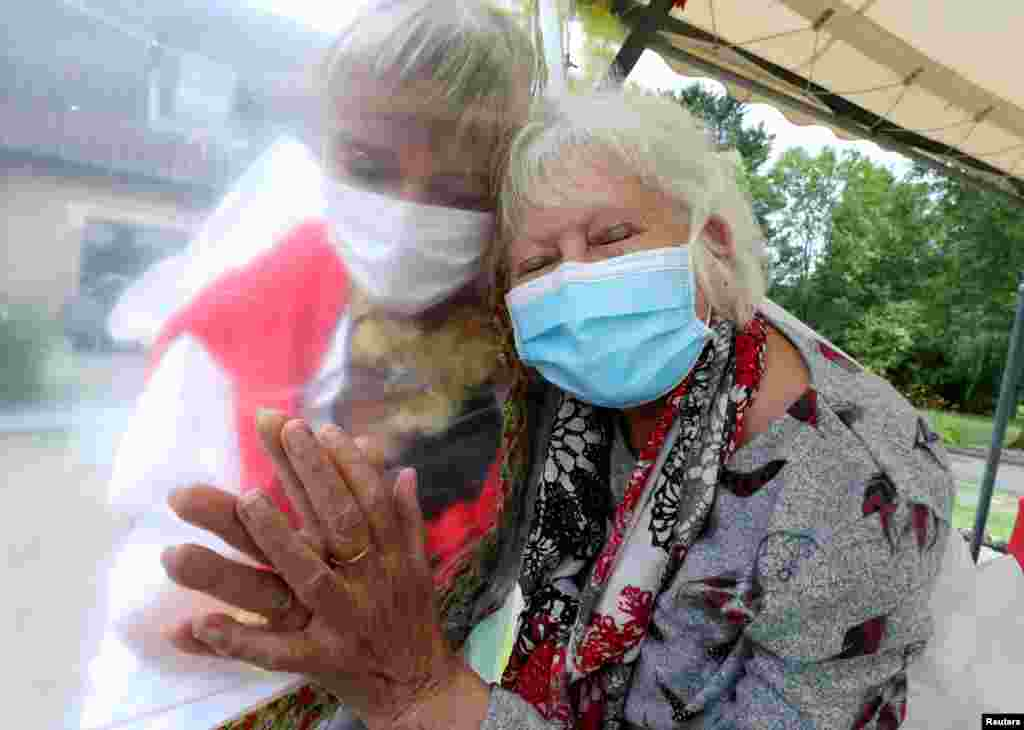 "Lily Hendrickx, 83, a resident at Belgian nursing home ""Le Jardin de Picardie"" hugs Marie-Christine Desoer, the director of the residence, through a wall made with plastic sheets to protect against potential coronavirus disease (COVID-19) infection, in Peruwelz, Belgium, July 1, 2020."