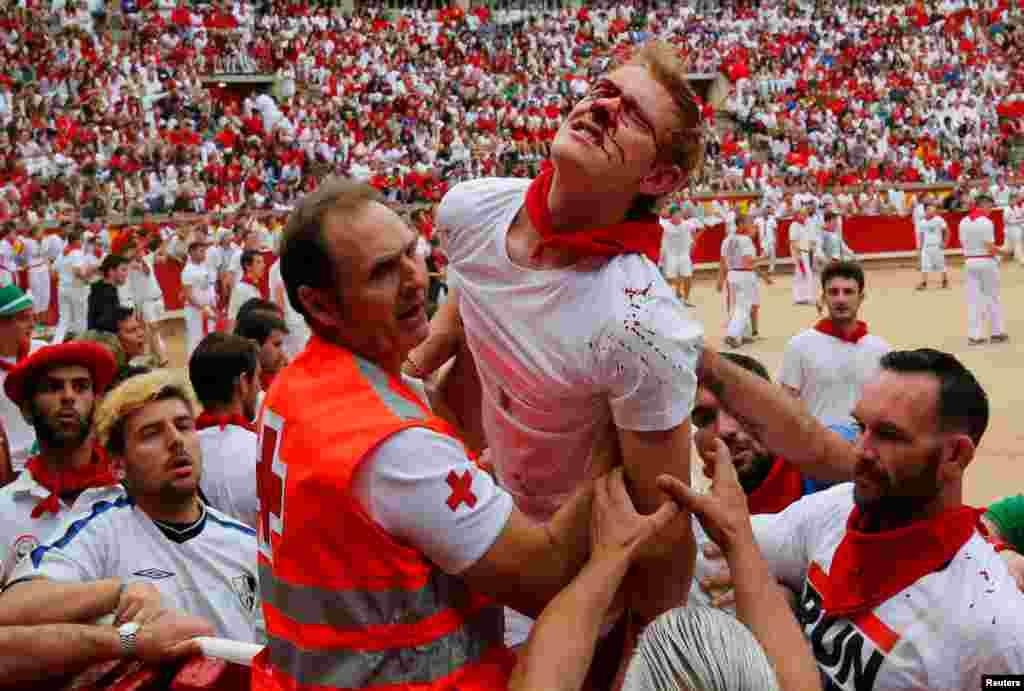 Petugas kesehatan membawa seorang peserta yang terluka dalam festival lari dikejar banteng 'San Fermin' di kota Pamplona, Spanyol.