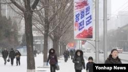 북한이 핵실험을 강행한 12일 오후 북한 시민들이 '장엄한 진군'이라고 쓰인 현수막이 내걸린 평양 거리를 걷고 있다.