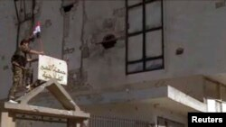 2013年6月5日效忠叙利亚总统阿萨德的一名军人在政府军占领了反政府战略城镇古赛尔之后在一座大门挂起叙利亚国旗。