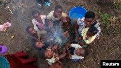 Une famille congolaise déplacée par des attaques des combattants du mouvement islamiste ougandais des Forces Démocratiques Allées (ADF), autour d'un feu, au camp de transit de Bukanga, à Bundibugyo, Ouganda, juillet 2013.