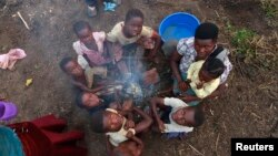 FILE - A Congolese refugee family displaced by fighting between the Congo army and a rebel group, Allied Democratic Forces (ADF), warm themselves around fire at Bukanga transit camp in Bundibugyo, Uganda, July 2013.