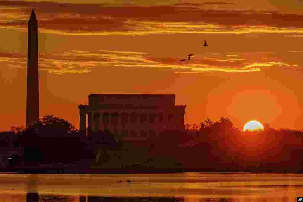 ព្រះអាទិត្យរះនៅក្បែរវិមានរដ្ឋធានីវ៉ាស៊ីនតោននិង Lincoln Memorial តាមដងទន្លេ Potomac River រដ្ឋធានីវ៉ាស៊ីនតោន។