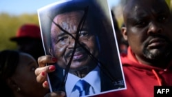 FILE - People protest Cameroon's President Paul Biya on Pennsylvania Avenue near the White House, Oct. 22, 2018 in Washington. In Cameroon, Security forces have been cracking down on street rallies protesting the October 7 re-election of President Paul Biya.