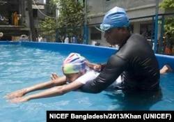 An instructor teachers a boy to swim in Bangladesh, 2013. (Photot Courtesy of UNICEF/Khan)