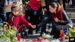 Seorang perempuan dan anak perempuan menyalakan lilin di sebuah memorial untuk para korban bom di Place de la Bourse, Brussels (26/3).(AP/Geert Vanden Wijngaert)