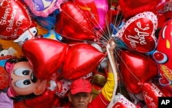 A vendor sells balloons on Valentine's Day in Manila, Philippines, Feb.14, 2017.