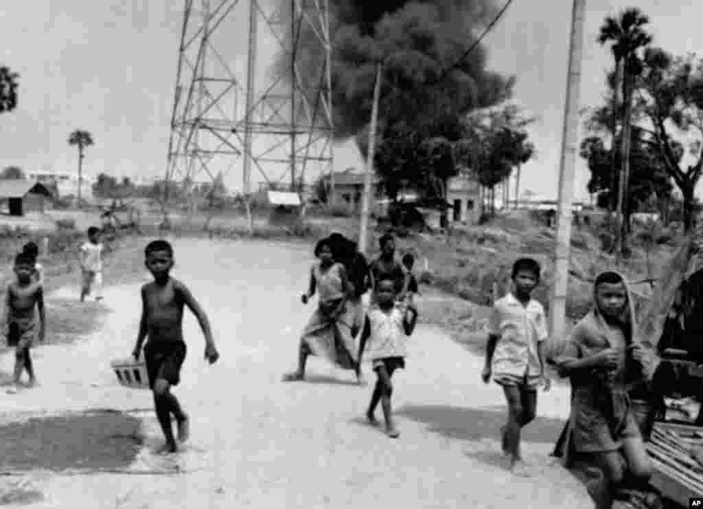 Children run from burning buildings set on fire by rocket attacks near Phnom Penh Airport in Cambodia, the day the city was taken by Khmer Rouge troops, April 17, 1975. (AP Photo)