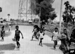 FILE-Children run from burning buildings set on fire by rocket attacks near Phnom Penh Airport in Cambodia, the day the city was taken by Khmer Rouge troops, April 17, 1975. (AP Photo)