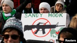 FILE - People hold signs memorializing Sandy Hook Elementary School, where 26 children and adults were killed in a mass shooting in December 2012, as they participate in the March on Washington for Gun Control on the National Mall in Washington, January 26, 2013.