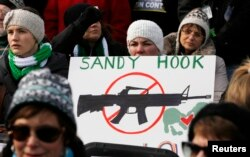 People hold signs memorializing Sandy Hook Elementary School, where 26 children and adults were killed in a mass shooting in December, as they participate in the March on Washington for Gun Control on the National Mall in Washington, January 26, 2013.