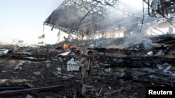 Seorang pejuang Houthi berjalan melewati lokasi serangan udara koalisi pimpinan Saudi di Sana'a, Yaman, Minggu (5/11).
