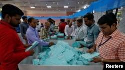 Anggota staf pemilu India menyortir surat suara sebelum menghitungnya di sebuah TPS di Ahmedabad, India, 23 Mei 2019.