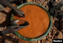 An artisanal miner pans for gold using a plastic wash basin and metal pan at an unlicensed mine near the city of Doropo, Ivory Coast, Feb. 13, 2018.
