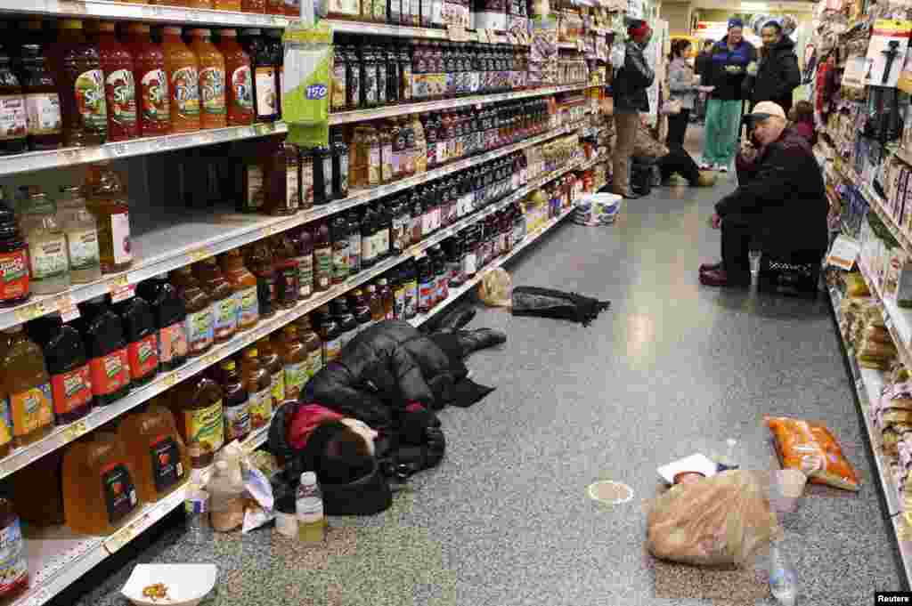 People rest in the aisle of a Publix grocery store after being stranded due to a snow storm in Atlanta, Georgia.