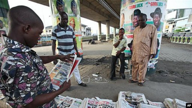 An Unidentified man reads a newspaper with the headline 'National Shame' after the election was postponed Saturday by Election Commission Chairman Attahiru Jega, Lagos, Nigeria, April 3, 2011