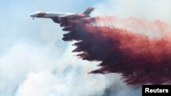 A plane drops fire-retardant chemicals on the 416 Fire near Durango, Colorado, June 9, 2018.