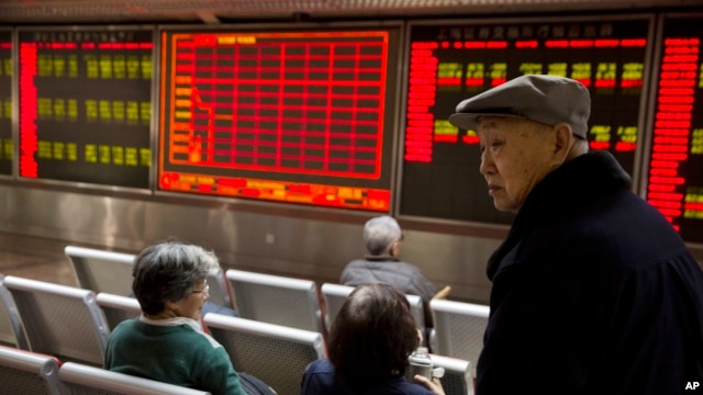 Investors gather near a display board showing the plunge in the Shanghai Composite Index at a brokerage in Beijing, China, Thursday, Jan. 7, 2016.