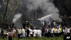 FILE - Cuba's President Miguel Diaz-Canel, third from left, walks away from the site where a Boeing 737 plummeted into a yuca field in Havana, Cuba, May 18, 2018.