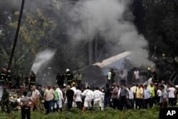El presidente de Cuba, Miguel Diaz-Canel, tercero desde la izquierda, se aleja de un campo de yuca donde cayó un Boeing 737 con más de 100 personas a bordo. Habana, Cuba. Mayo 18, 2018.