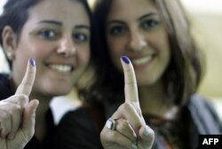 Egyptian women show their inked fingers after voting in Cairo, Egypt, Monday, Nov. 28, 2011