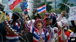 Demonstran anti-pemerintah Thailand meneriakkan keinginan mereka agar PM Yingluck Shinawatra mundur dari jabatannya, dari luar kantor sementara Yingluck di kantor Kementerian Pertahanan Thailand di Bangkok, Thailand (19/2).