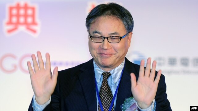 China Mobile Chief Executive Li Yue waves to the press during a ceremony in Taipei linking the first undersea fiber optic cable between Taiwan and China on January 18, 2013.