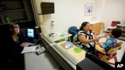 Spesialis klinis Catey Funaiock (kiri) mengamati Marlaina Dreher bermain dengan anaknya, Brandon, 5, dalam sebuah program di Marcus Autism Center di Atlanta, Georgia, AS. (Foto: Dok)