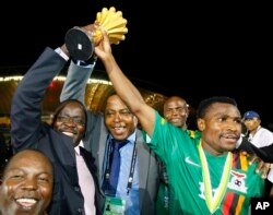 Zambia's captain Christopher Katongo, right, and Zambia Football President Kalusha Bwalya, second right, hold up the Africa Cup trophy after their victory over Ivory Coast in Libreville, Gabon, Feb. 12, 2012.