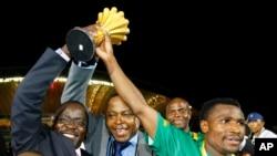 Le capitaine zambien Christopher Katongo, à droite, et le président de la Fédération zambienne de football Kalusha Bwalya, brandissent le trophée de la CAN 2012 après leur victoire contre la Côte d'Ivoire à Libreville, Gabon, le 12 février 2012.