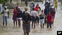 Residents leave flooded homes in a low-lying area affected by Tropical Storm Isaac in Port-au-Prince, Haiti Aug. 25, 2012 (UN photo)