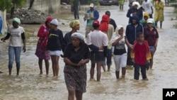 Cư dân rời bỏ nhà cửa bị ngập lụt trong một khu vực ở Port-au-Prince, Haiti, ngày 25/8/2012