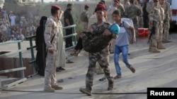 Irački vojnik pomaže devojčici raseljenoj posle borbi u Ramadi, 19. maj 2015.