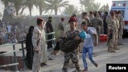 ທະຫານອີຣັກຄົນນຶ່ງ ກຳລັງອູ້ມເດັກນ້ອຍຜູ້ຍິງ ຂ້າມຂົວຢູ່ນອກ ນະຄອນຫລວງ Bagdad.