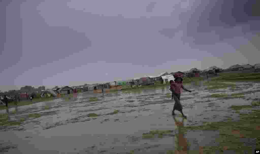 An internally displaced Rohingya woman walks carrying a sibling in a makeshift camp in Sittwe, Burma, May 14, 2013.
