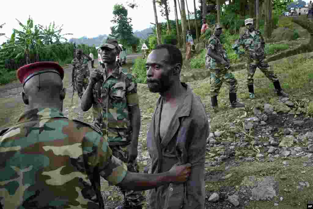Congolese M23 rebel fighters detain a man they suspect to be an FDLR (Force Democratique de Liberation du Rwanda) rebel returning from an incursion into Rwanda Near Kibumba, north of Goma Nov. 27, 2012.