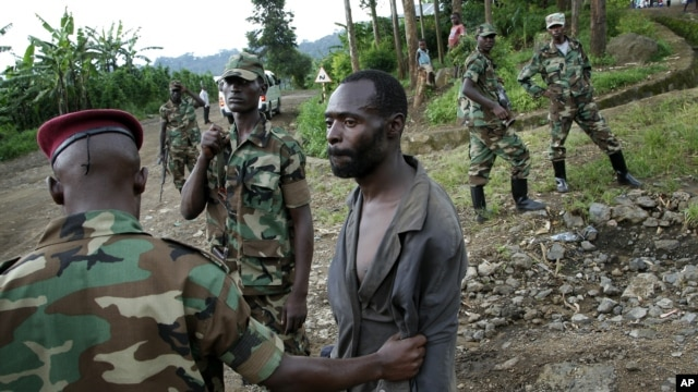 Congolese M23 rebel fighters detain a man suspected to be an FDLR rebel returning from an incursion into Rwanda near Kibumba, north of Goma, November 27, 2012.
