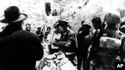 Arhiva - Na fotografiji od 8. juna 1967. ortodoksni Jevrejin nudi molitveni šal izraelskim vojnicima koji se mole kod Zida plača u Jerusalimu u Izraelu dan nakon šestodnevnog rata (AP Photo)