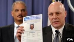 Egzekitif asistan direktè FBI a Shawn Henry kap montre yon papye kriminè leta ameriken ap cheche pandan yon koferans pou laprès nan washington ak Minis jistis ameriken an, Eric Holder