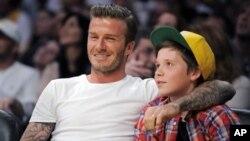 Bintang sepakbola David Beckham (kiri) duduk disamping puteranya, Brooklyn, menyaksikan pertandingan basket NBA di Los Angeles (foto: dok).