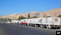 A convoy of humanitarian aid waits in front of the United Nations Relief and Works Agency (UNRWA) offices before making their way into the government besieged rebel-held towns of Madaya, Zabadani and Moadimayet al-Sham in the Damascus countryside, as part of a U.N.-sponsored aid operation, in Damascus, Syria, Feb. 17, 2016.