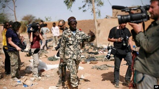 Um soldado maliano acenando aos jornalistas para abandonarem o local