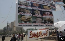 FILE - Egyptian protesters walk under a banner portraying detained journalists. It reads 'The military council protects the former regime.' Another banner calls for 'Media purification,' Tahrir Square, Cairo, Egypt, July 10, 2011
