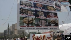 Egyptian protesters walk under a big banner with pictures of some journalists. It reads 'The military council protects the former regime.' Another banner calls for 'Media purification,' Tahrir Square, Cairo, Egypt, July 10, 2011