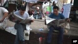 星期六埃及开罗广场上抗议者在读报,同时全国等候总统决选结果