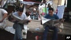 Người biểu ở Quảng trường Tahrir đọc báo, chờ kết quả bầu cử (ngày 23 tháng 6, 2012)