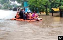 Pasukan Tanggap Bencana Nasional India menyelamatkan orang-orang yang terdampar di banjir di Kolhapur, di negara bagian Maharashtra, India barat, Jumat, 23 Juli 2021. (AP)