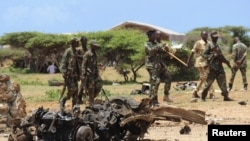 FILE - Jubaland forces walk near the site of an Aug. 22, car bomb attack near a military training base south of Mogadishu.