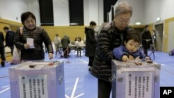 A boy places his grandmother's vote into a ballot box at a polling station in Tokyo, Japan on Dec. 16, 2012.