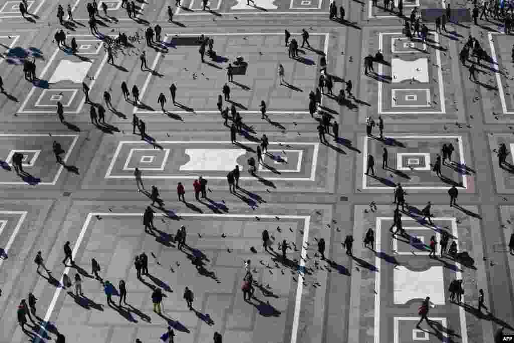 People walk across Duomo square, Milan, Italy.
